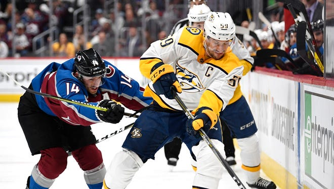 Nashville Predators defenseman Roman Josi (59) moves the puck defended by Colorado Avalanche left wing Blake Comeau (14) during the first period of game 4 in the first round NHL Stanley Cup Playoffs at the Pepsi Center, Wednesday, April 18, 2018, in Denver, Colo.
