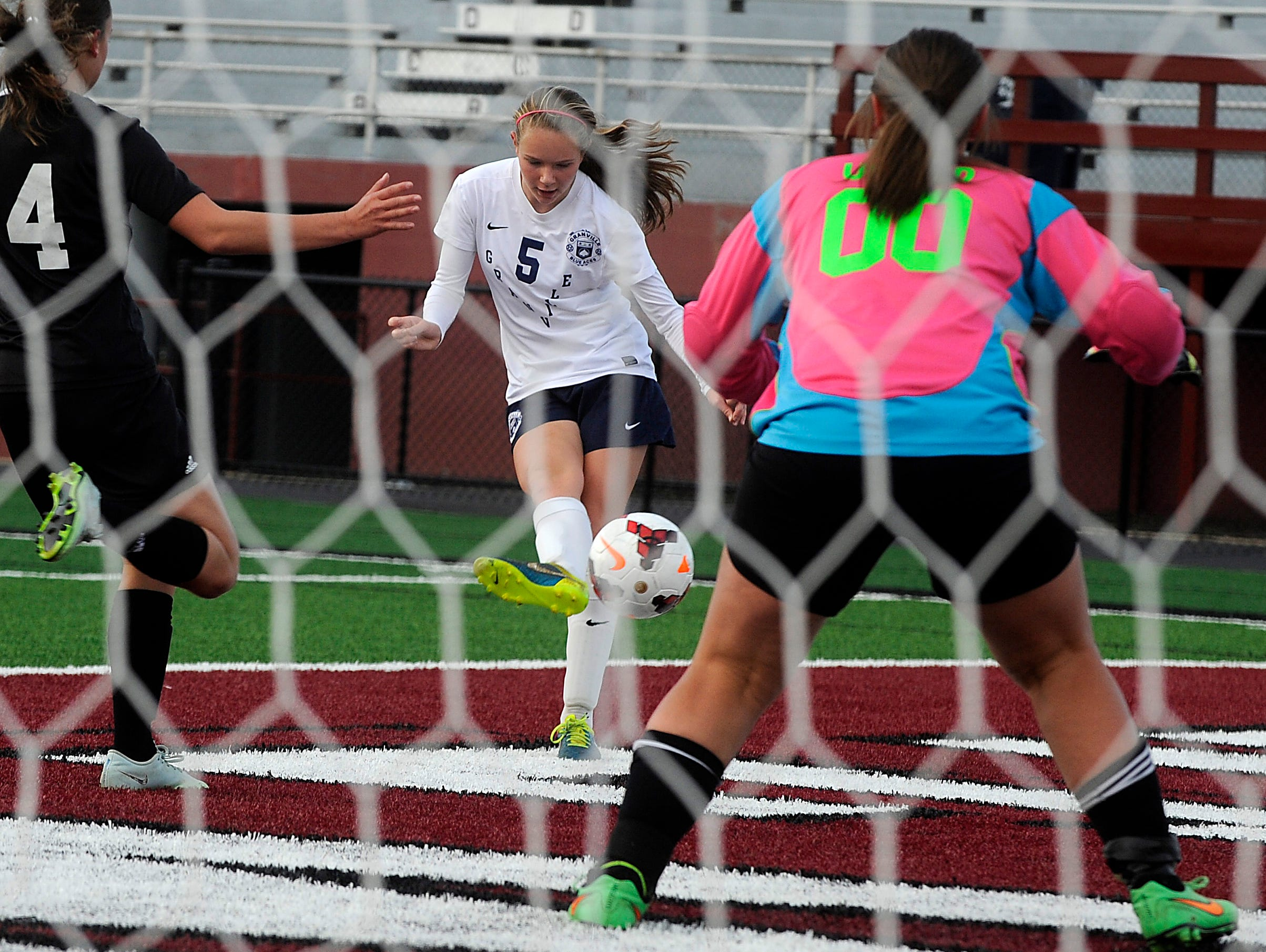 Granville's Gracie Dennison takes a shot on goal against defense from Tri-Valley's Liken Little and keeper Emily Untied. Granville defeated Tri-Valley 10-1 in the Division II regional final on Saturday, Nov. 7, 2015, at White Field in Newark. The Blue Aces will advance to play Indian Hill in the state tournament.