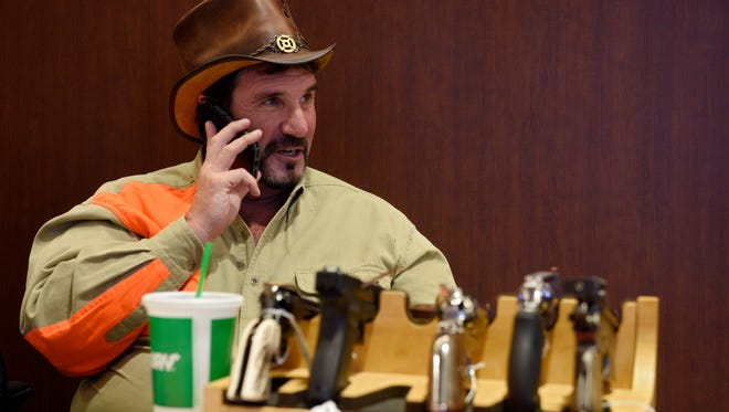 Richard Larson, owner of Last Chance Auction Company, talks on the phone at his booth in the Sioux Falls Regional Airport on Friday, Oct. 20, 2017. Larson setup the booth including a gun display to encourage out-of-state pheasant hunters to attend his company's auction on Thursday.