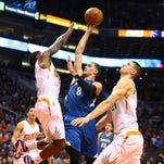 Minnesota Timberwolves guard Zach LaVine (8) drives to the basket against Phoenix Suns guard Eric Bledsoe (2) and center Alex Len (21) in the first half at Talking Stick Resort Arena Sunday.