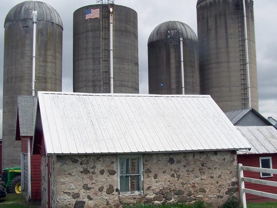 A smokehouse and a colony of upright silos illustrate