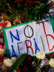 The words 'Not Afraid' are written on a sign that hangs in front of a sea of flowers in front of the French embassy in Berlin, Germany on Nov. 15.