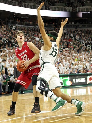 Feb 26, 2017; East Lansing, MI, USA; Wisconsin Badgers forward Ethan Happ (22) is defended by Michigan State Spartans forward Kenny Goins (25) during the first  half of a game at the Jack Breslin Student Events Center. Mandatory Credit: Mike Carter-USA TODAY Sports