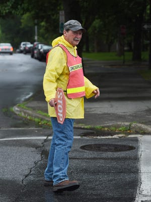 John T. Lawrence, 67, a crossing guard working with the Poughkeepsie City School District, helps get a few students across at the corner of Market Street and Montgomery Street in the City of Poughkeepsie.
