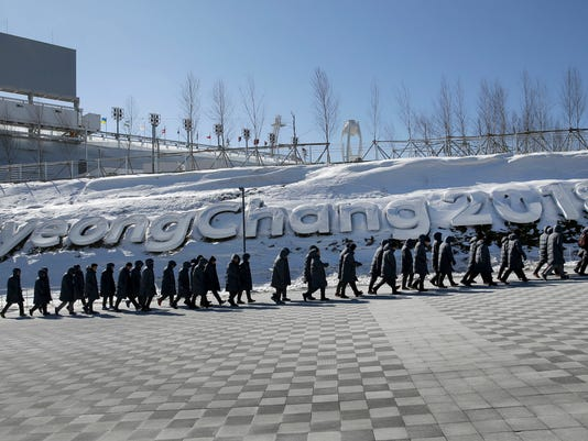 Workers walk up a ramp at the Pyeongchang Olympic Plaza as preparations continue for the 2018 Winter Olympics in Pyeongchang, South Korea, Monday, Feb. 5, 2018. (AP Photo/Charlie Riedel)