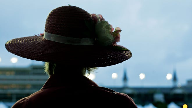 A woman watches morning workouts at Churchill Downs April 29. in Louisville, Ky.