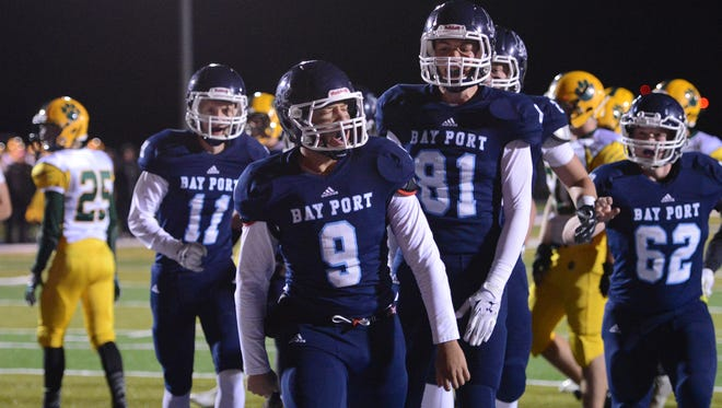 Bay Port's Alec Ingold (9) celebrates with teammates, including Zach Lorbeck (81), Logan White (11), and Gunnar Brosz, after scoring a touchdown against Ashwaubenon.