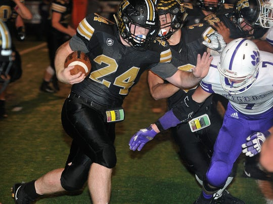Henrietta quarterback Zack West (24) powers his way for good yardage as Jacksboro defenseman Ty Kennedy (7) moves in for the tackle.