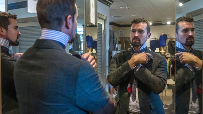 Employee Wes Davis ties a tie at Levy's Clothier for Men & Women. The store sells designer apparel and accessories and stocks brands from around the world.