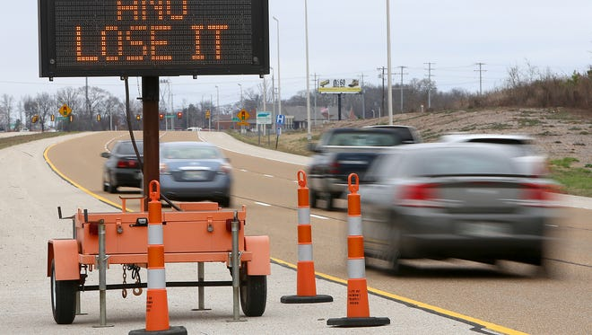 "Traffic flows in front of a ""Booze It and Lose It"" sign along the Highway 45 Bypass on Wednesday."