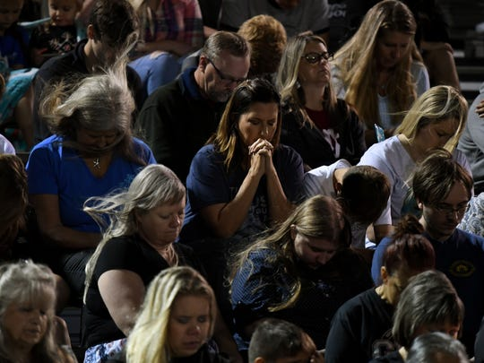 People pray during a memorial service for victims of
