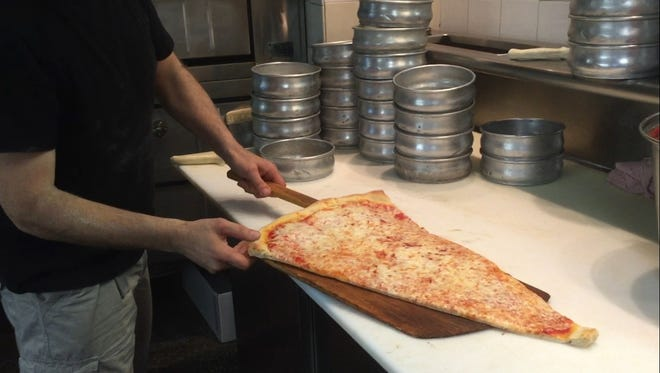 Pizza Barn owner Angelo DeLuca takes a piping hot Super Slice straight from the oven.