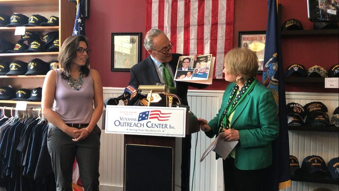 Lindsay Cray (left), Sen. Chuck Schumer (middle) and Congresswoman Louise Slaughter (right), as Schumer holds up photos of Lindsay's father Tom, a Rochester Vietnam veteran fighting glioblastoma.