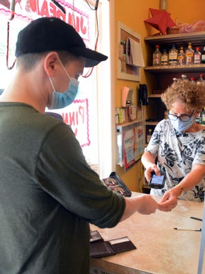 Betsy Eichholz, owner of Towne Liquor Store, uses a new ID scanner to scan the driver's license of Bryan Lavigne, 35, of Bozrah Friday for a purchase at her business in Norwichtown.