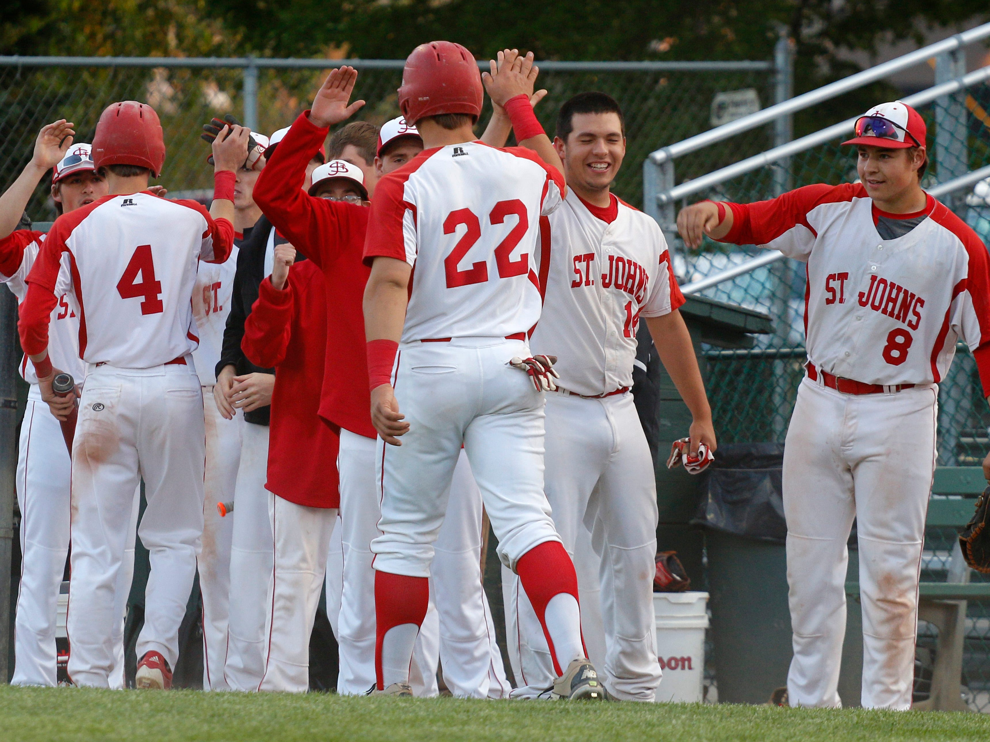St. Johns' Alex Hudak (4) and Adam Proctor (22) are congratulated after scoring against Haslett during their Diamond Classic game Thursday, May 21, 2015, in Lansing, Mich.