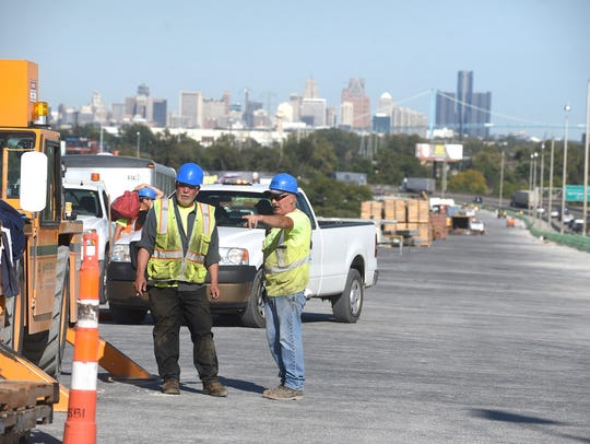 The Detroit skyline is seen in the background as work