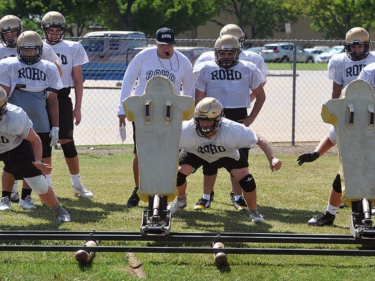Offensive linemen for the Rider Raider football team work on blocking technique using the three-man sled in an earlier 2018 practice session.