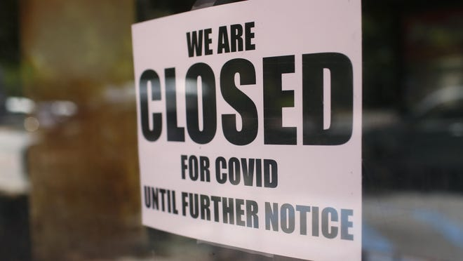 A closed sign in a downtown window in Athens, Ga, on Friday, May 1, 2020. Following Gov. Brian Kemp's decision to end the state's shelter-at-home order, some businesses elected to stay closed for financial or health reasons.