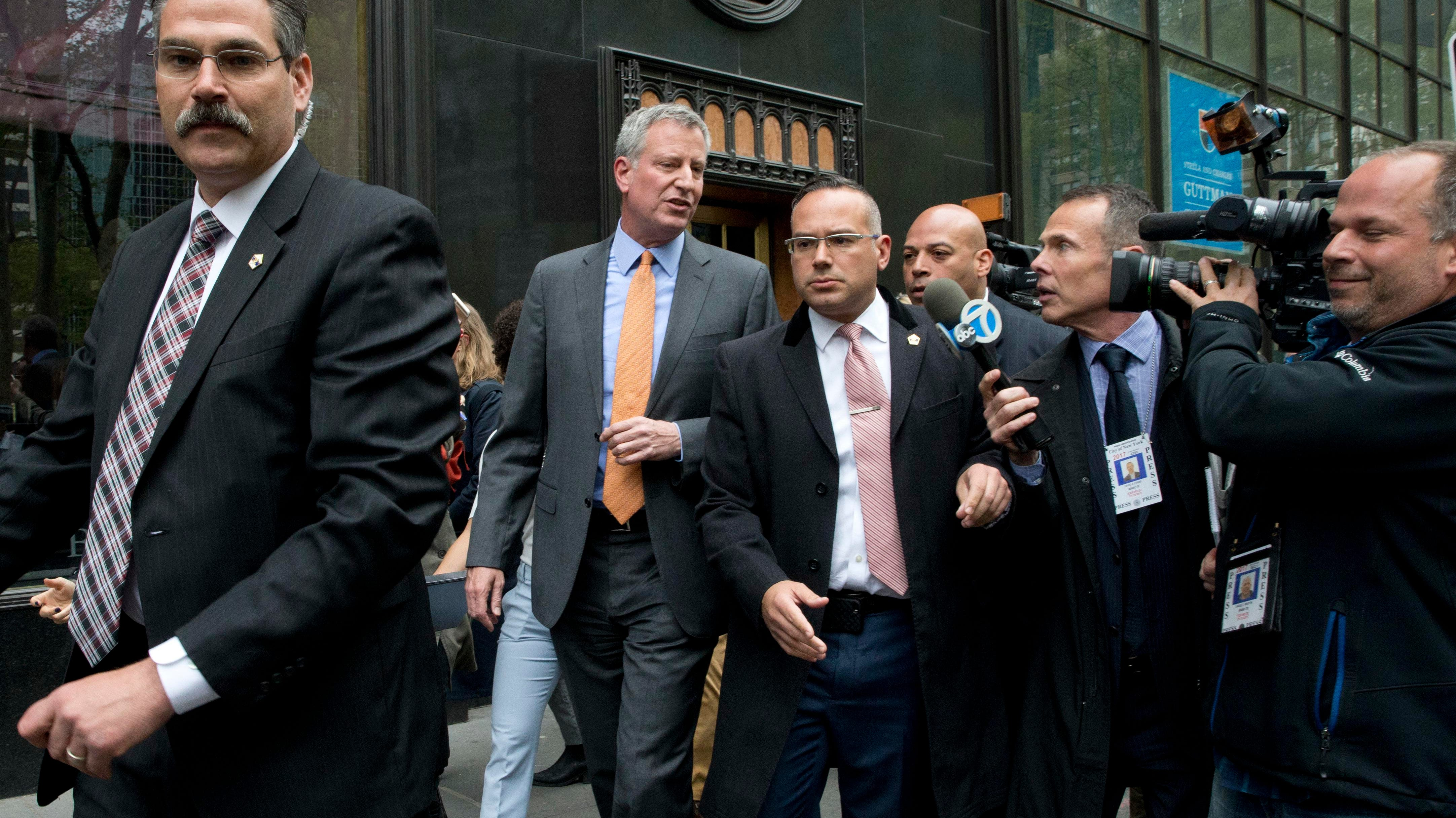 New York City Mayor Bill de Blasio, second from left, is surrounded by security and followed by reporters as he leaves an event April 28, 2016, in New York.