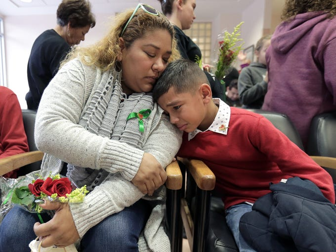 Olga Grays comforts her son, Angel Herrera, 9, as the