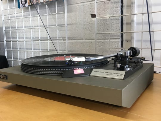 A turntable spins a record a Rogue Planet Music, a