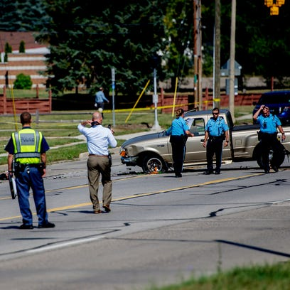 Lansing police investigate the scene of a serious motorcycle-truck