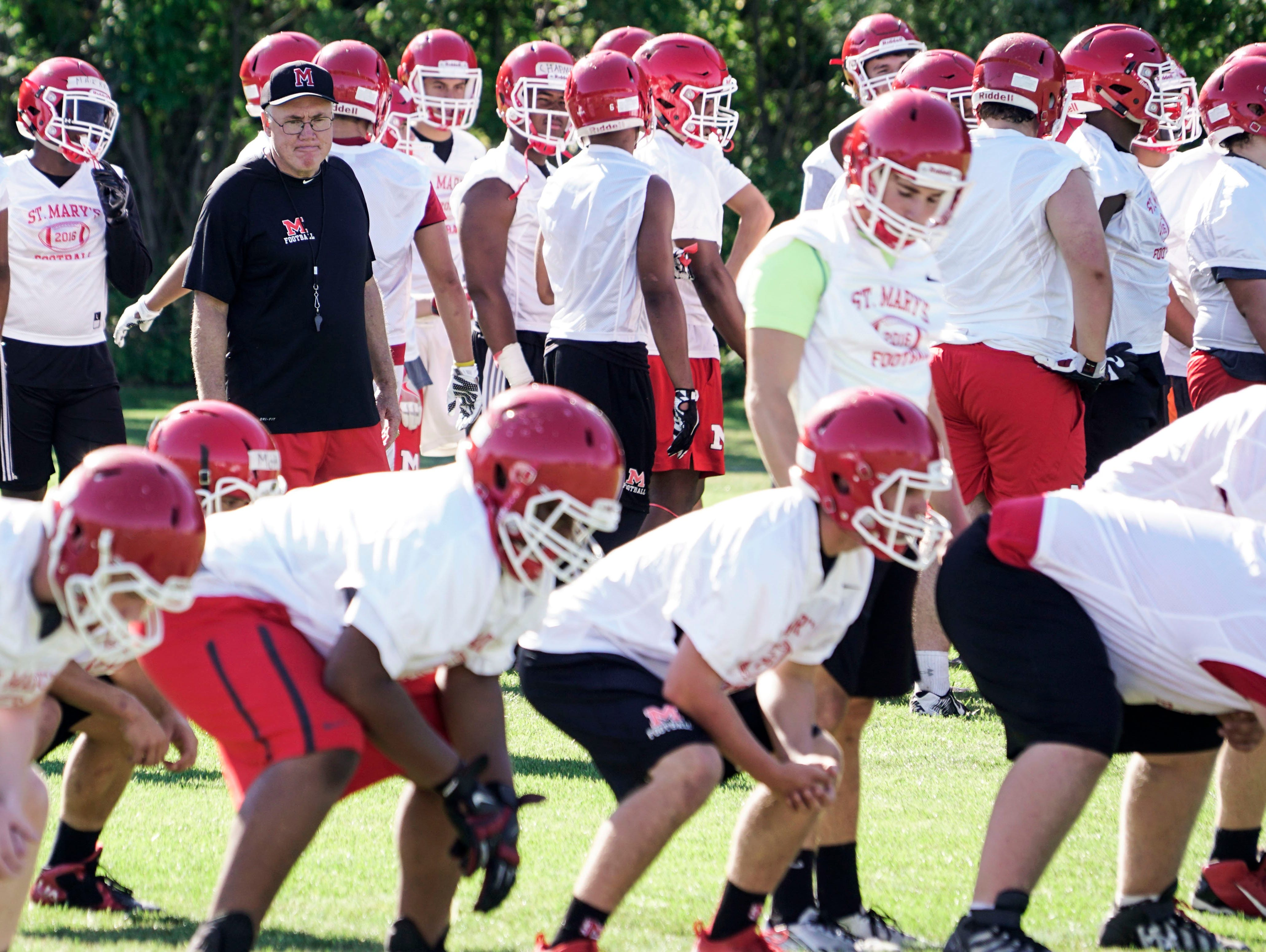 Head coach George Porritt, left, watches as the team runs drills during the first Orchard Lake St. Mary's High School football practice on Monday, Aug. 8, 2016 at Orchard Lake St. Mary's High School in Orchard Lake Village.