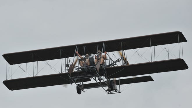 """Pilots of the Wright """"B"""" Flyer replica wave to the crowd as they fly over a crowd in 2010."""