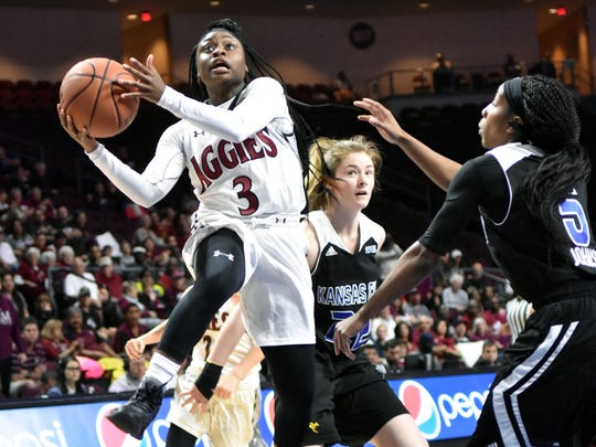 New Mexico State's Tonisha Childress splits two Missouri-Kansas City defenders and goes in for an uncontested layup during Friday afternoon's action at the WAC Women's Basketball Tournament held in Las Vegas, Nevada.