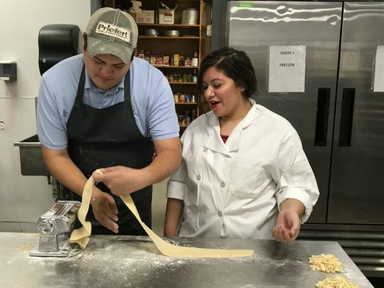 Anthony Grafta shows Alexia Hinojosa, a second-year students in the Culinary Arts program at Central High School how to make pasta on Friday, Sept. 8.