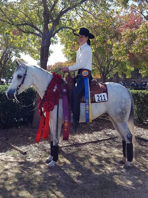 """Lindsey Smith McCool, a 2000 graduate of Mountain Home High School, recently won the U.S. National Championship in Amateur Half Arabian Reining in Tulsa, Okla., at the Arabian National Championship Horse Show. McCool was riding her horse, Hustle Up, who was bred at Pine Meadow Farm in Mountain Home.""""Hustler"""" was bred specifically for this event, and nine years later, he and McCoolreached their goal of a National Championship.Riders and horses had to earn qualifying scores in competitions over the last 12months to reach the national show.In the final round McCooland """"Hustler"""" were the first to ride in a class of 21 horses. Their score of 407 held up as the top score to win the championship."""