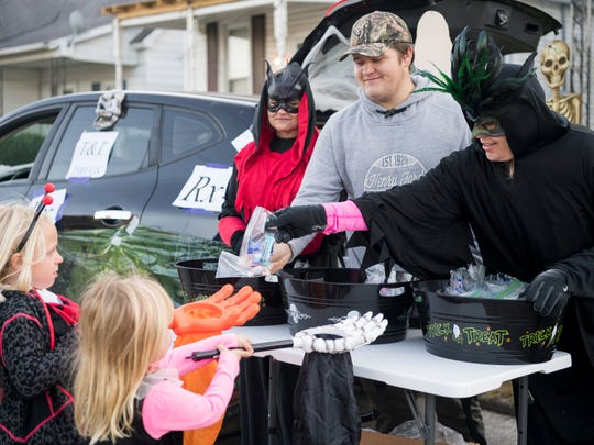 Patti Marshall (right to left), Landon Nelson and Pam Marshall with T&T Drug Store hand out candy to Emma, 4, and Lily Kelton, 5, during the  Community Trunk or Treat Extravaganza in Henderson last year. This year it returns on Saturday, Oct. 27, at 3 p.m.
