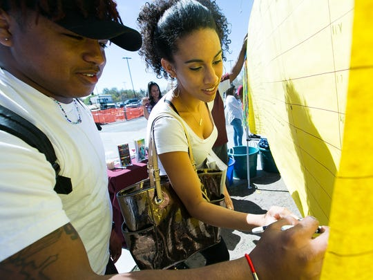 """New Mexico State University students Daveon Ellis, 22, left, and Kaily Madden, 20, fill out a """"Never have I ever"""" poster during a recent spring break safety event hosted by WAVE."""