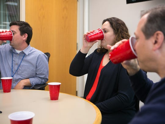 Testing Dogfish Head's first canned beer in a blind taste test in the newsroom with Scott Goss (from left), Sarika Jagtiani and Dave White.