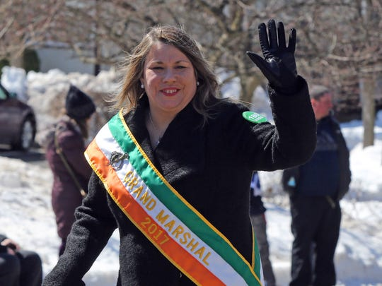 Grand Marshal Carmel Reilly waves while walking in the Pearl River St. Patrick's Day Parade on Sunday.