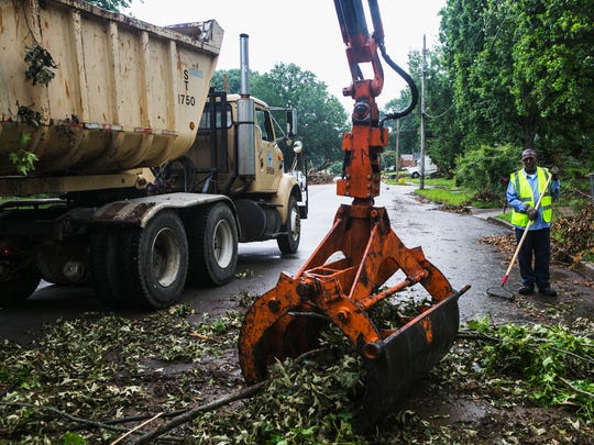 June 4, 2017 - Gerald Jeffreys, with the City of Memphis, watches tree debris being collected by colleague Darcy Cheatham as they clean up Durham Ave. in Frayser Sunday afternoon. Crews from the City of Memphis worked to remove fallen trees and debris from the area as a result of last week's storm that left thousands of people without power. MLGW's outage map shows 6,500 customers are still without power as of noon Sunday.
