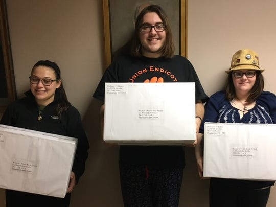 Maria Roma, VP Orion Barber and Heather Coggin, hold boxes full of the 116 books contributed to the project.
