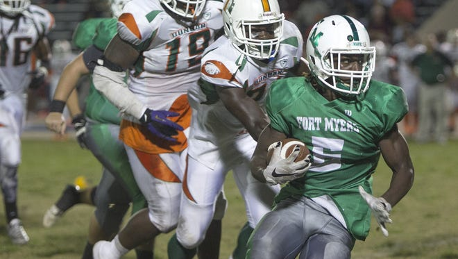 Fort Myers' Darrian Felix, right, tries to out run Dunbar defenders Donovan Gayle and Shanon Reid for positive yards Friday night.