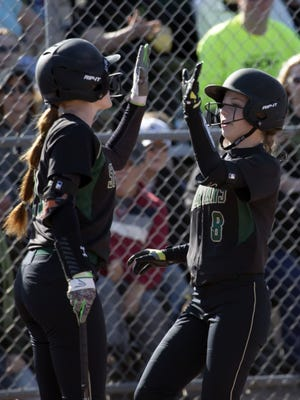 Oshkosh North's Courtney Day (8) is congratulated by Sydney Supple after scoring a run in the first game of Friday's doubleheader against Oshkosh West.