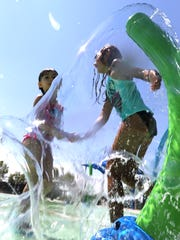 Addison Adeams-Payan, left, and Leila Owen play in the water at the new spray park at Sue Young Park in northeast El Paso.