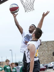 Bryson Langdon goes up for a shot playing 3-on-3 street ball in the Gus Macker tournament. This year, the festival will take place in the Menominee Nation Arena.