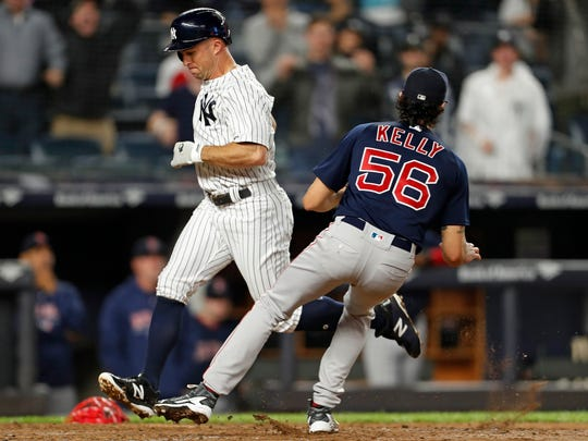 New York Yankees left fielder Brett Gardner (11) scores a run on a wild pitch by Boston Red Sox relief pitcher Joe Kelly (56) during the seventh inning at Yankee Stadium.