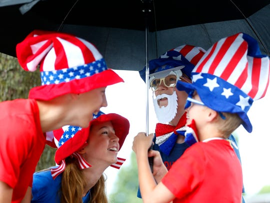 From left Ian Williams, 12, Lilly Williams, 10, Tyler Douglas, 12, and Will Douglas, 9, play around under an umbrella before the start of the 27th annual Midtown Old Fashioned 4th of July Parade and Celebration on Tuesday, July 4, 2017.