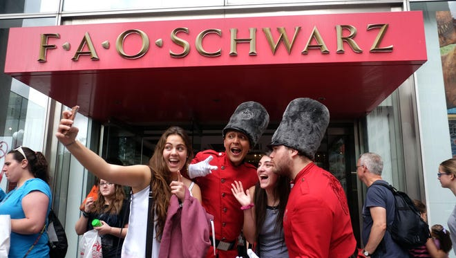 People have their picture taken at the entrance of the iconic toy store FAO Schwarz in New York. The 153-year-old store, founded by German immigrant Frederick August Otto Schwarz, has become embedded in popular culture.