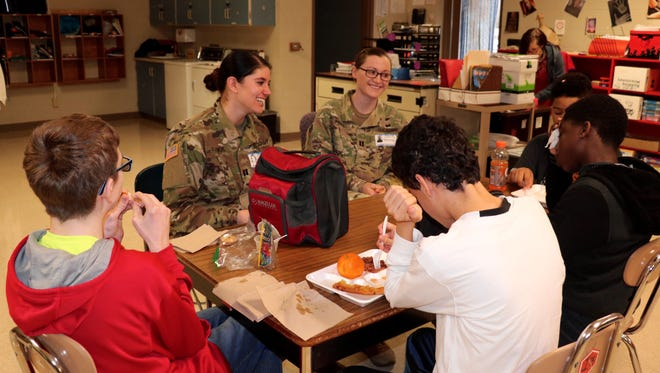 Blanchfield Army Community Hospital Soldiers, Capt. Lilly Vanek and Capt. Breanna Price talk with students from Northeast Middle School during lunch, Feb. 14. Soldiers and civilians from Blanchfield volunteer at the middle school through the Partners in Education program. Partners in Education works to unite schools with local businesses and organizations for the benefit of the entire community. U.S. Army photo by Maria Yager.