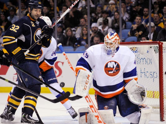 Buffalo Sabres' John Scott (32) battles for a rebound after a save from New York Islanders' Anders Nilsson (45), of Sweden,  during the first period of an NHL hockey game in Buffalo, N.Y., Sunday April 13, 2014. (AP Photo/Gary Wiepert)