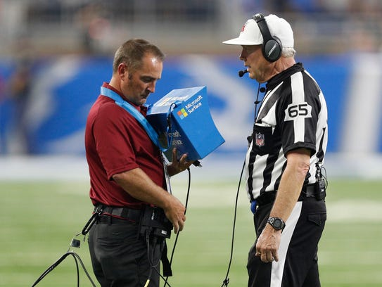 NFL referee Walt Coleman looks at the instant replay