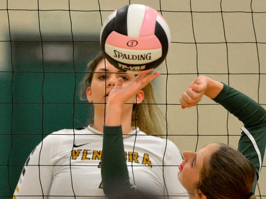 Ventura's Reyn Hoffman watches as La Reina's Jenna Matus sets the ball Wednesday night at the varsity girls volleyball match hosted by La Reina in Thousand Oaks.