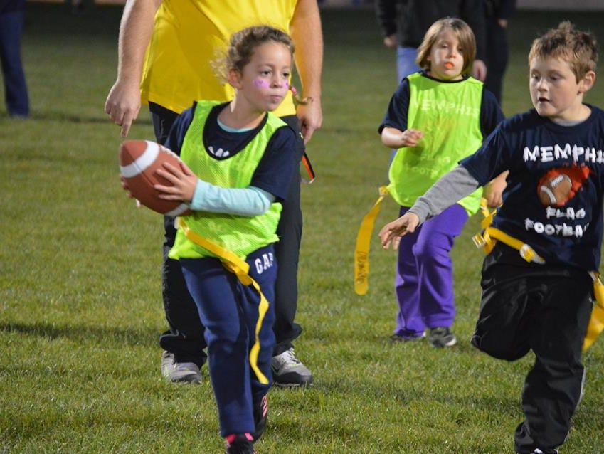 Ava Kuroski runs away from the defense during Memphis flag football's game under the lights on Oct. 11.