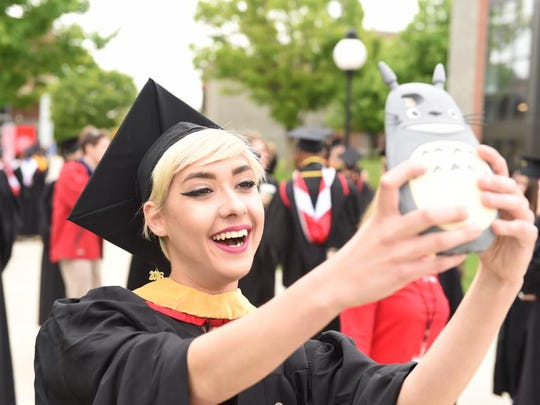 Poughkeepsie native Melissa Laffin uses her phone to FaceTime with her family prior to commencement at Marist College Saturday.